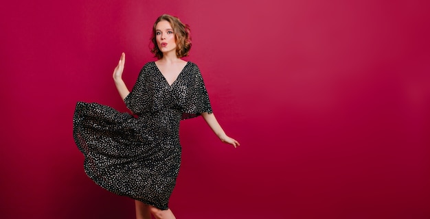 Incantevole ragazza sottile in eleganti scarpe tacco alto ballando su sfondo bordeaux Foto Gratuite