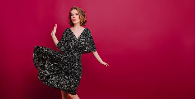 クラレットの背景で踊るエレガントなハイヒールの靴で魅惑的なスリムな女の子 無料写真