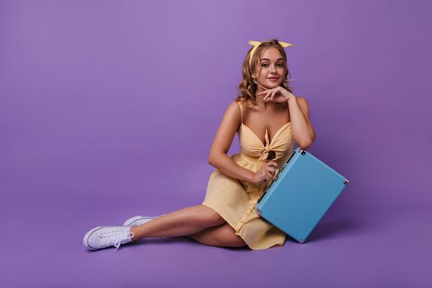 Incantevole donna abbronzata indossa scarpe di gomma seduta sul pavimento con elegante valigia. ritratto di ragazza riccia allegra in posa dopo il viaggio. Foto Gratuite