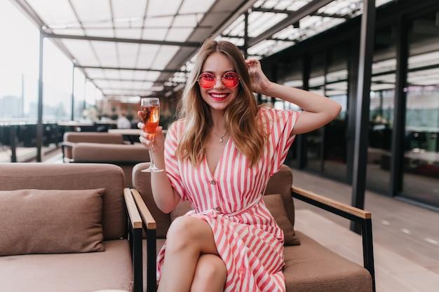 와인 글라스와 함께 손에 포즈 핑크 선글라스에 매혹적인 백인 여자. 카페에서 편안한 스트라이프 드레스에 매력적인 여자를 웃 고있다. 무료 사진