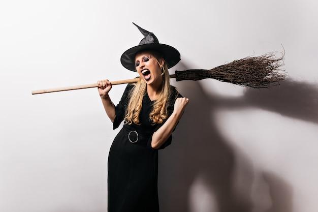 Очаровательная ведьма в черном наряде наслаждается вечеринкой. удивительный блондин волшебник с метлой. Бесплатные Фотографии