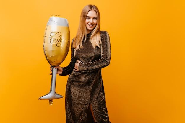 링 스파클 드레스 생일을 축하하는 매혹적인 여자. 큰 와인 글라스와 오렌지에 서 서 웃는 예쁜 여자의 초상화. 무료 사진