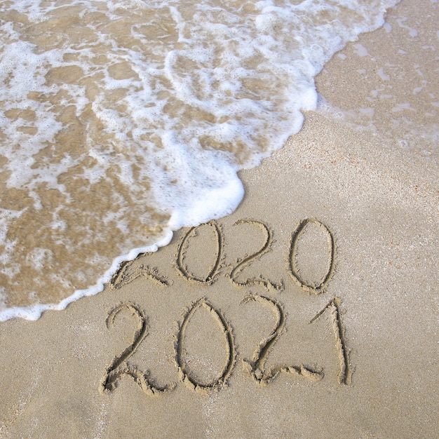 End of the year 2020 concept. new year 2021. inscription in the sand on the beach Premium Photo