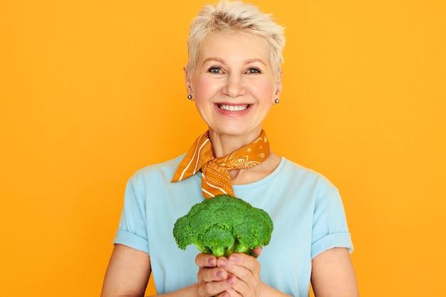 緑のブロッコリーを手に孤立したポーズをとる短い白髪のエネルギッシュな美しい中年女性は、健康的なオーガニックサラダを作りに行きます。 無料写真
