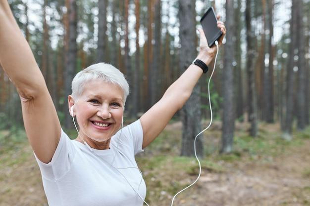 エネルギッシュで元気な引退した女性で、スリムなボディにフィットし、屋外でイヤホンでポーズをとり、手を上げ、携帯電話を持っています 無料写真