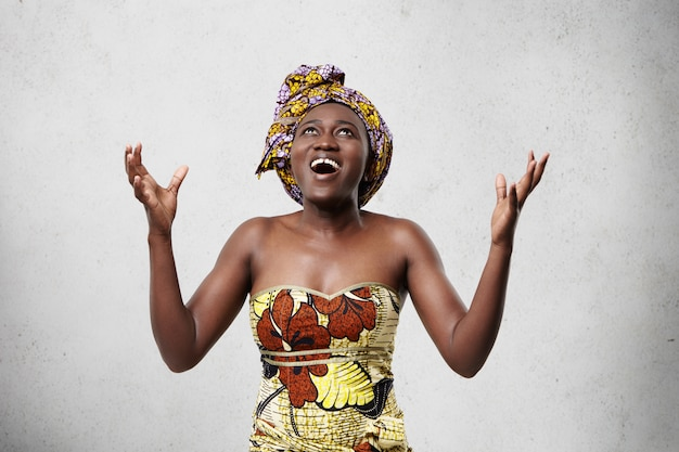 Energetic glad woman with dark skin wearing scarf on head and fashionable dress looking up raising her hands with excitement being thankful to god for life-saving. thankful middle-aged african woman Free Photo