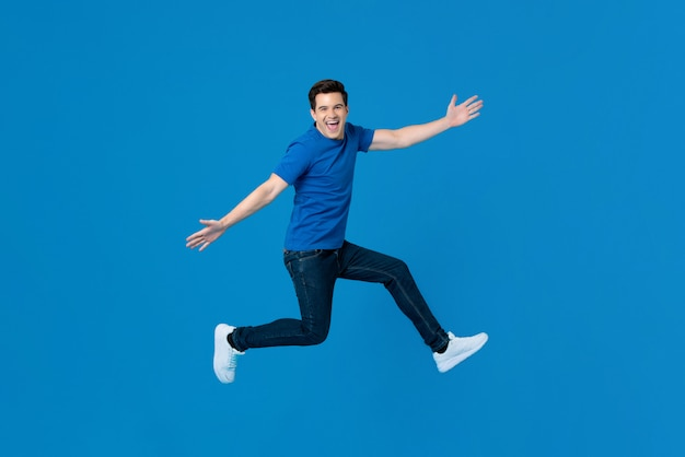Energetic handsome man jumping and smiling with outstretched hands Premium Photo