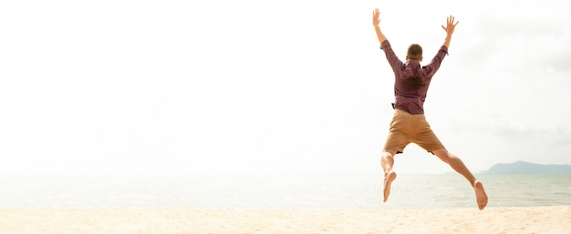 Energetic happy man jumping at the beach on summer holidays Premium Photo