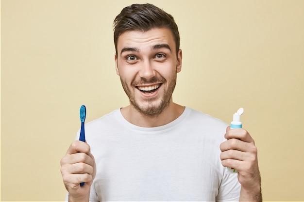 Giovane positivo energico con stoppie in posa con spazzolino da denti e pasta sbiancante che sorride ampiamente con denti bianchi perfetti. abitudini sane, routine quotidiana e cure dentistiche Foto Gratuite