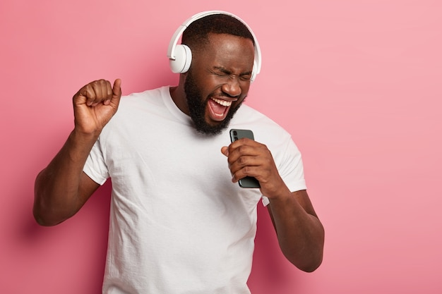 Energized black unshaven man sings to music, moves actively, wears headphones and casual t shirt, poses against pink background, keeps mouth widely opened Free Photo