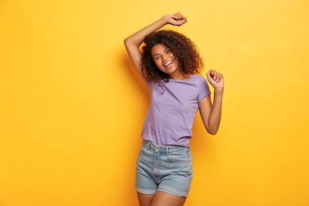 エネルギッシュな幸せなアフリカ系アメリカ人の女の子は、元気で、好きな音楽に合わせて踊り、スリムな体型で、カジュアルな服を着て、楽しく手を上げます 無料写真