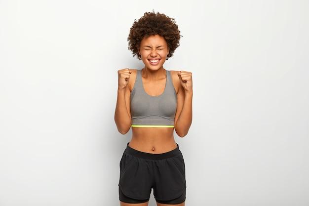 활력이 넘치는 스포티 한 여성은 승리를 기뻐하고, 주먹을 움켜 쥐고, 넓게 미소를 짓고, 스포츠 브래지어를 착용하고, 넓게 미소를 짓고, 흰색 배경 위에 절연되어 있습니다. 무료 사진