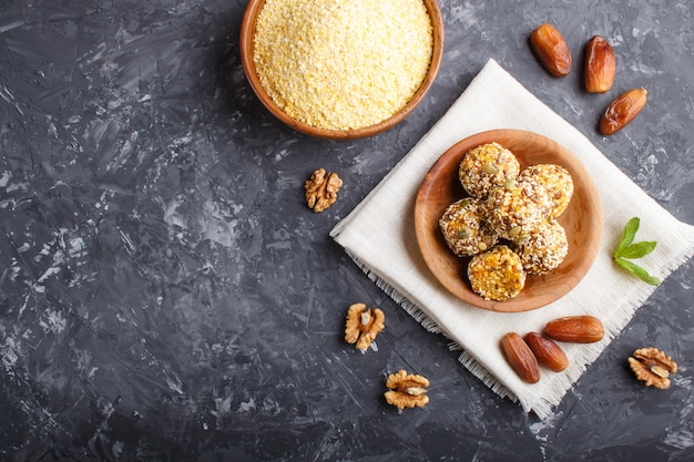 Energy ball cakes with dried apricots, cornflakes, sesame, linen, walnuts and dates Premium Photo