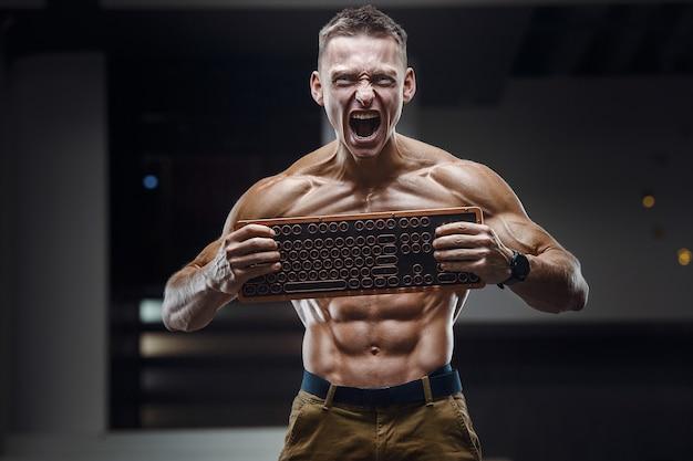 Кавказский человек энергии с криком клавиатуры. Premium Фотографии