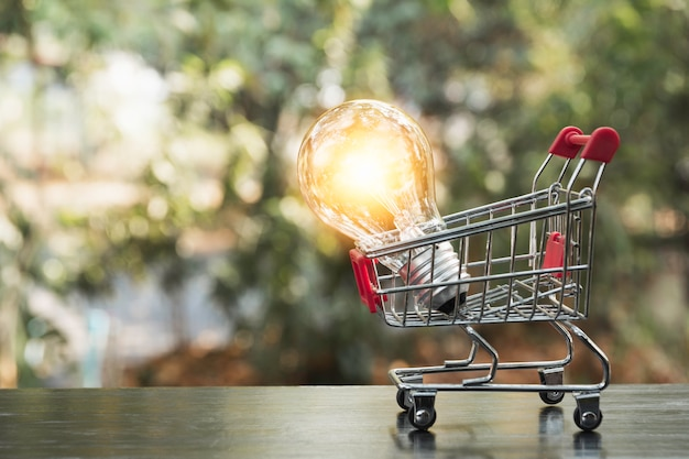 Energy saving light bulb with shopping cart financial and shopping concept Premium Photo
