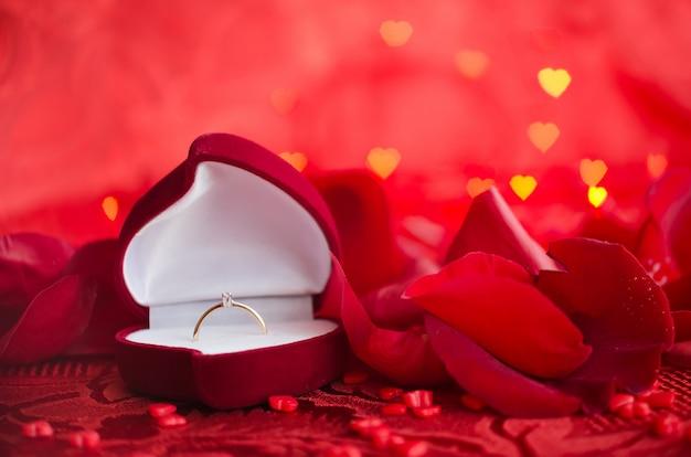 Engagement ring and red rose petals Premium Photo