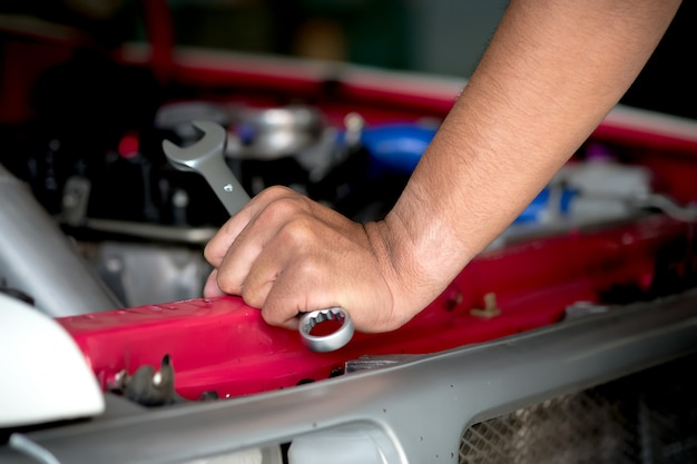 Engine repair technicians are hold the wrench in order to repair the car. Premium Photo