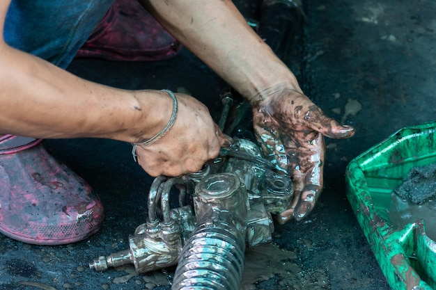 Engine repairman are using engine oil to wash parts of the engine. Premium Photo