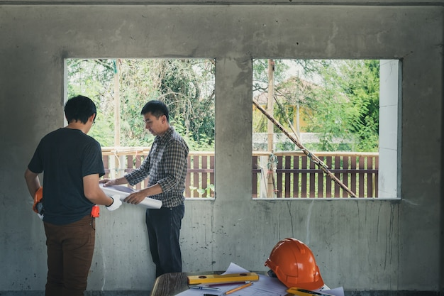 Engineer and architect discussing in building construction site. Premium Photo