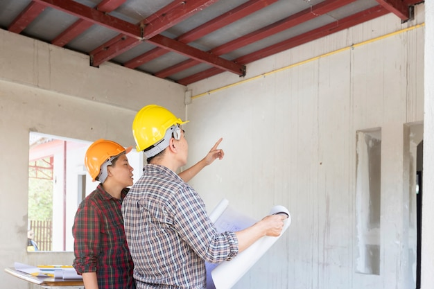 Engineer or architect discussing with foreman about project in building Premium Photo