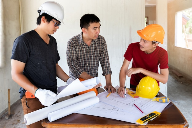 Engineer and architect discussing with foreman in construction site. Premium Photo