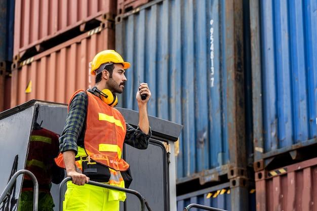 Инженер с бородой, стоящий с посудой в желтом шлеме, для контроля загрузки и проверки качества контейнеров с грузового судна для импорта и экспорта на верфи или в гавани Premium Фотографии