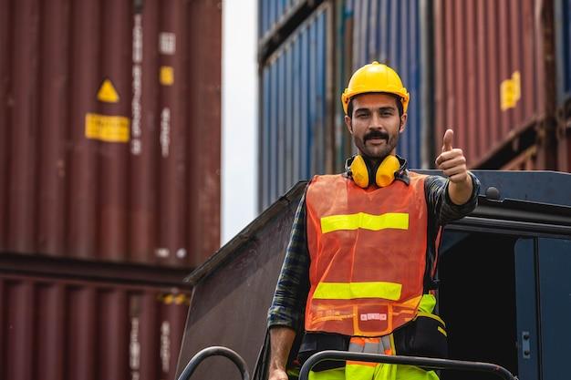 엔지니어 수염 남자는 노란색 헬멧을 도자기와 함께 서서 선적을 제어하고 조선소 또는 항구에서 수입 및 수출을 위해화물 화물선에서 컨테이너의 품질을 확인합니다. 프리미엄 사진