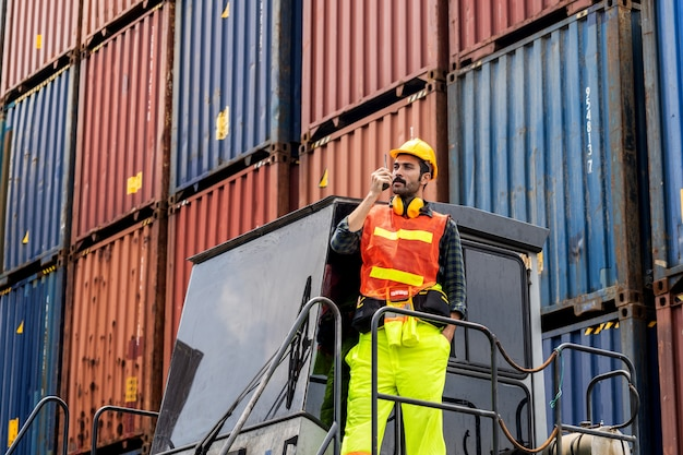 Engineer beard man standing with ware a yellow helmet to control loading and check a quality of containers from cargo freight ship for import and export at shipyard or harbor Premium Photo