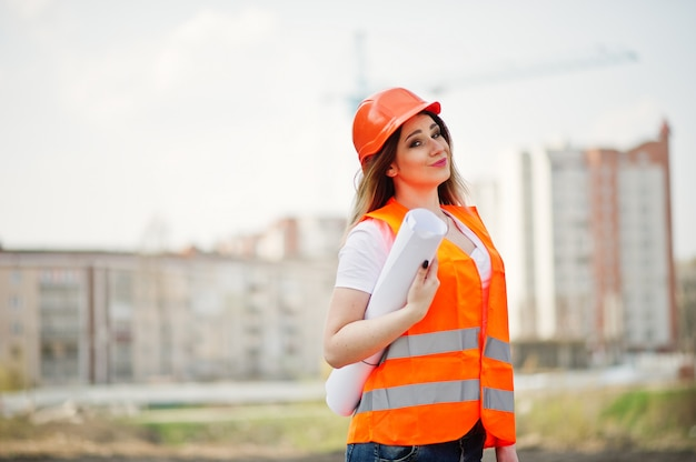Engineer builder woman in uniform waistcoat and orange protective helmet hold business paper against new buildings with crane. Premium Photo