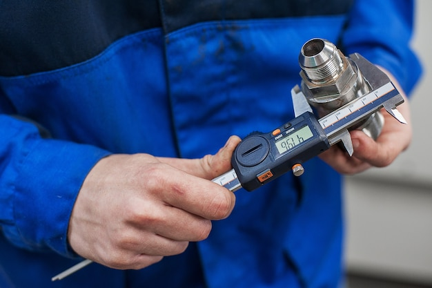 Engineer in factory with apprentice checks component quality Premium Photo
