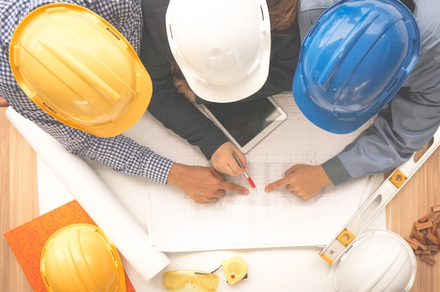 Engineer and foreman wearing safety helmet are meeting at site outdoor and pointing to drawing paper Premium Photo