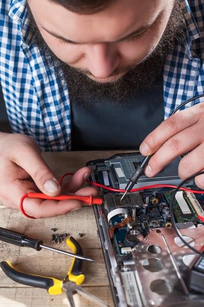 Engineer hands diagnostics laptop with multimeter Premium Photo