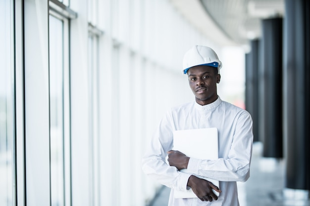 Engineer in hardhat standing with laptop computer in office near panoramic window Free Photo