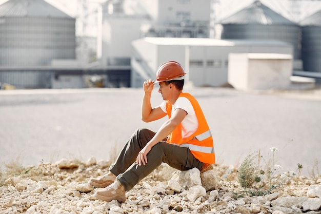 Engineer in a helmet sitting by the factory Free Photo