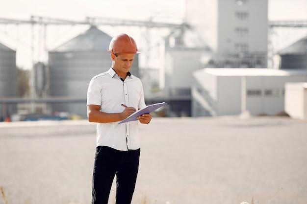 Ingegnere in un casco che fa una pausa la fabbrica Foto Gratuite