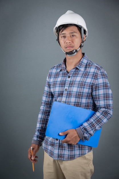 Engineer holding blueprints and reading notes on clipboard while standing on gray background. Free Photo