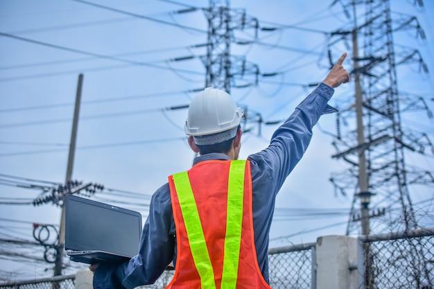 Engineer holding computer notebook high voltage power plant Premium Photo