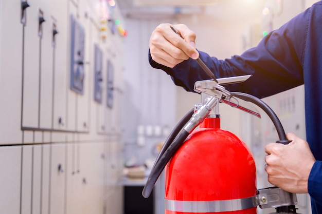 Engineer inspection fire extinguisher in control room. Premium Photo