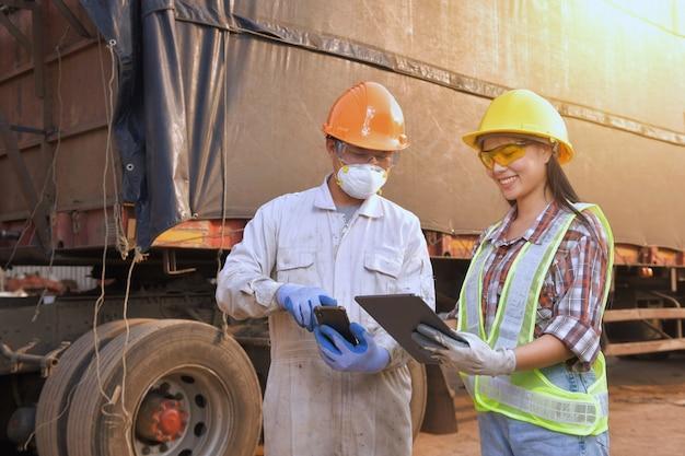 Инспектор-инженер, работающий на грузовике с фоном контейнера. бизнес концепции логистики и транспорта. Premium Фотографии