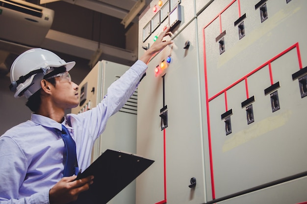 Engineer is check voltage or current by voltmeter in control panel of power plant. Premium Photo