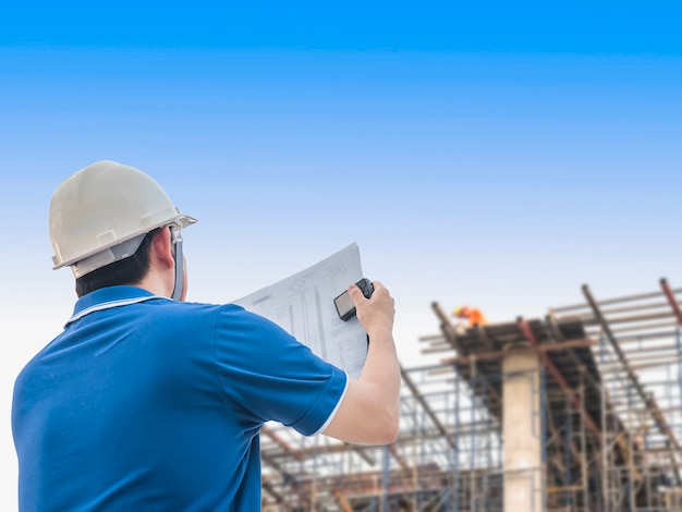엔지니어는 건물 건설 현장에서 자신의 작업을 검사하고 있습니다 무료 사진