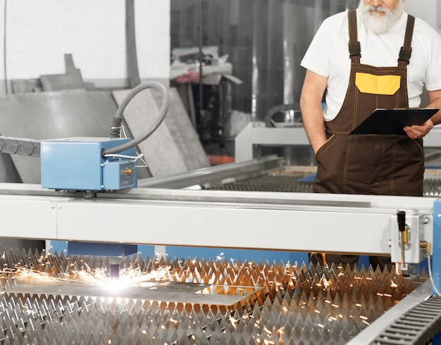 Ingegnere osservando la lamiera di taglio laser al plasma. Foto Gratuite