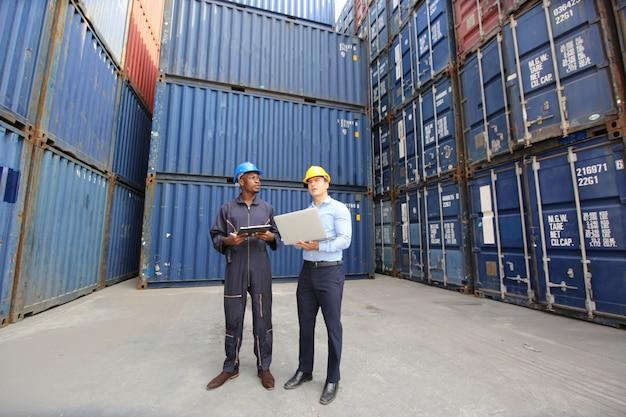 엔지니어 또는 감독관이 항구의화물에서 선적 컨테이너 상자를 확인하고 제어합니다. 프리미엄 사진