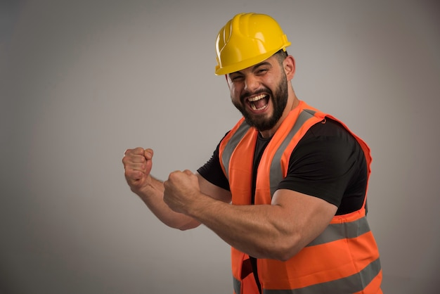 Ingegnere in uniforme arancione e casco giallo con grandi muscoli. Foto Gratuite