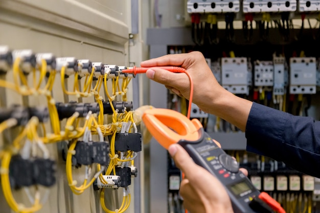 Engineer tester measuring  voltage and current  in electical cabinet control Premium Photo