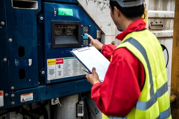 Инженер использовал ноутбук и контролировал температуру контейнерного ящика. Premium Фотографии