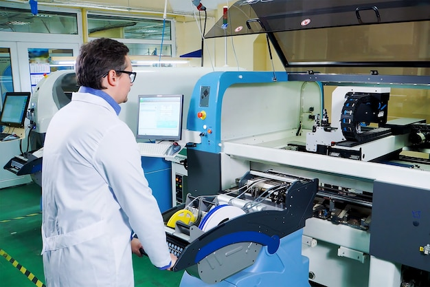 The engineer in a white robe and glasses works for the surface mount technology machine. Premium Photo