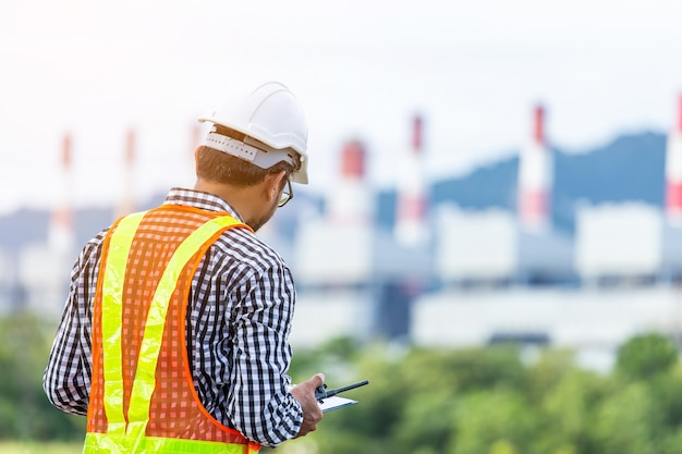 Engineer with a coal power plant in the background, thailand. Premium Photo