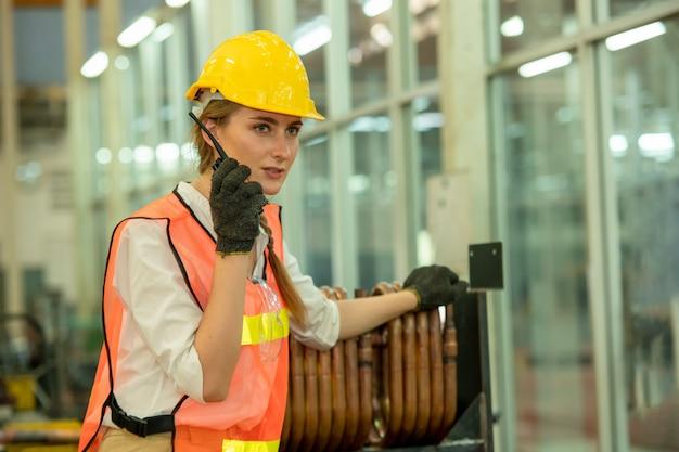 공장에서 무선 통신을 사용 하여 엔지니어 여자, 작업에 대 한 여성 정비공 사용 무 전기 야. 프리미엄 사진