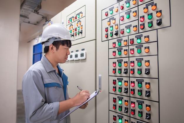Инженер работает и проверяет состояние электрической панели в помещении hvac Premium Фотографии